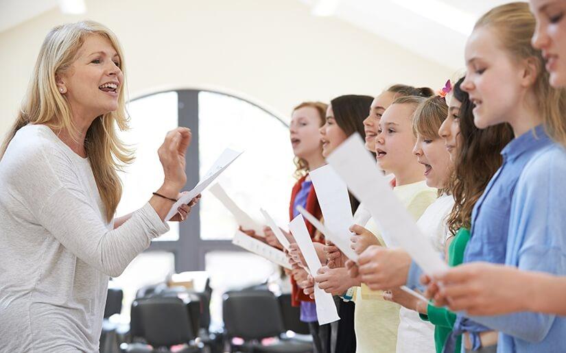 מורה למוסיקה מלמדת תלמידי בית ספר